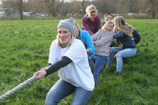 groep op grasveld met touwtrekken