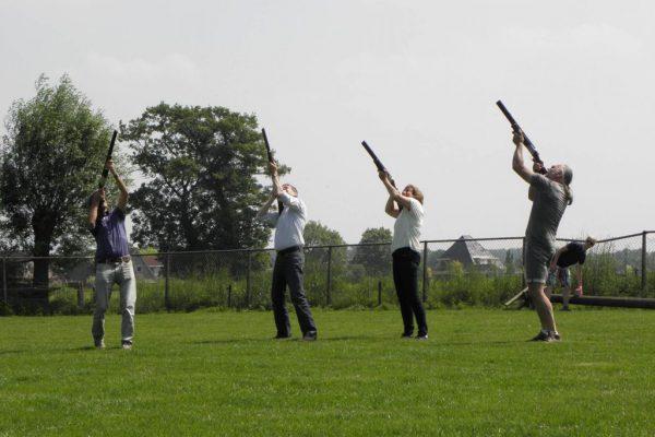 groep op grasveld schiet kleiduiven met laser