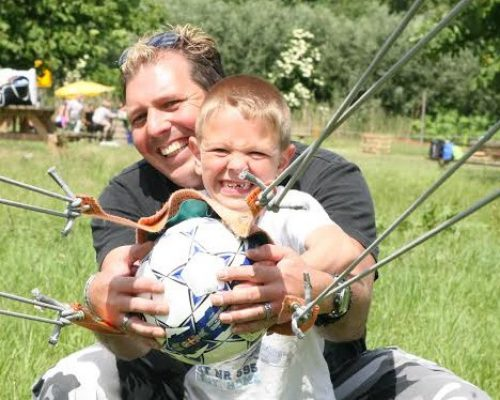 Vader en zoon met katapult en voetbal tijdens uitje