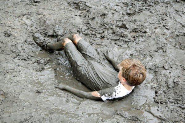 jongen speelt in modder