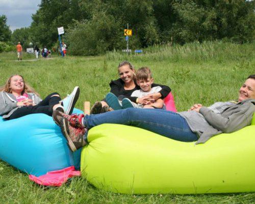 gezin zit ontspannen in het gras tijdens uitje