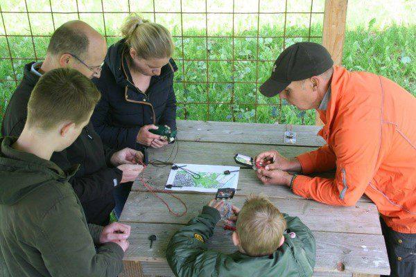 gezin krijgt uitleg over navigatie met kompas