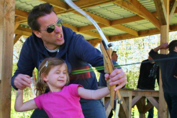 vader en dochter bezig met boogschieten tijdens uitje in Almere