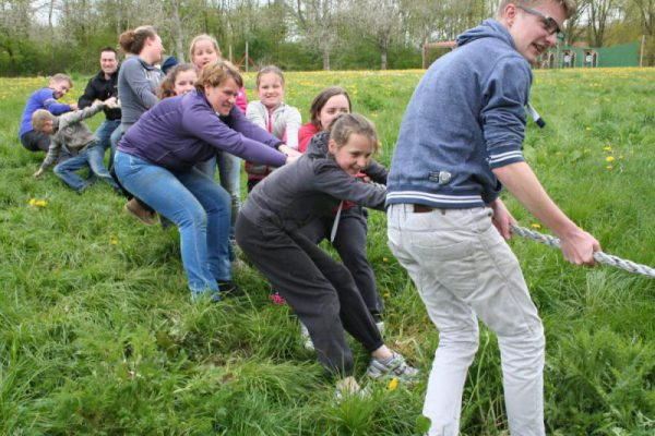 Familie bezig met touwtrekken in de natuur tijdens uitje