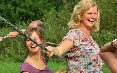 vrouwen lachen tijdens actief groepsuitje met gezin