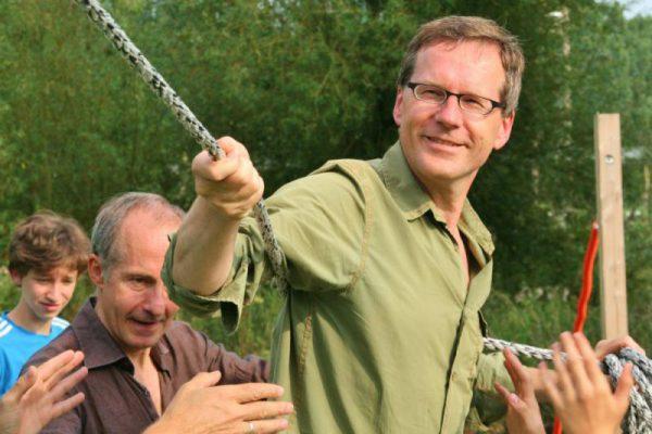 man met touw tijdens actief familie uitje in de natuur