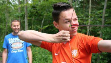 jongen met oranje shirt schiet met boog