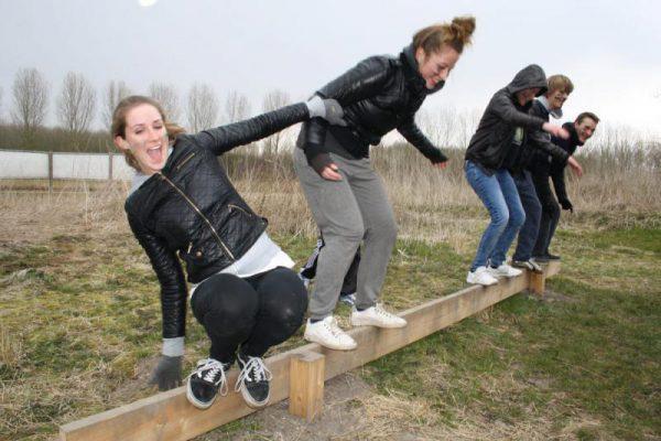 groep op evenwichtsbalk tijdens actief uitje