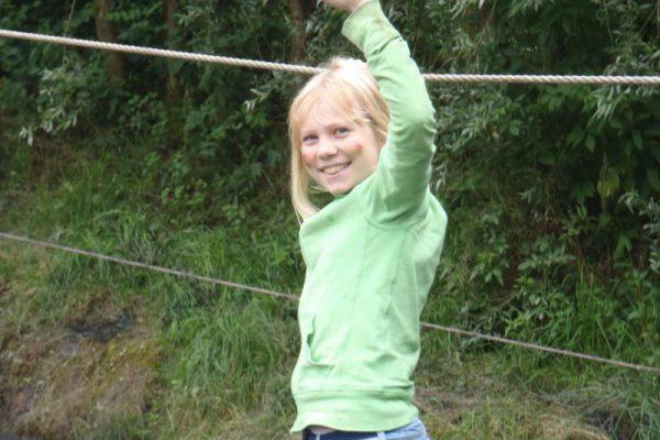 Meisje op touwbrug tijdens vakantie-uitje