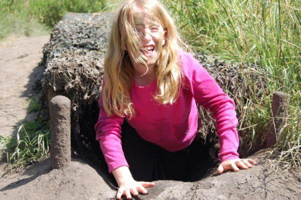 Meisje uit camotunnel tijdens actief kinderfeestje buiten in de natuur