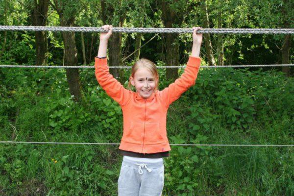 meisje op junglebrug in het voorjaar