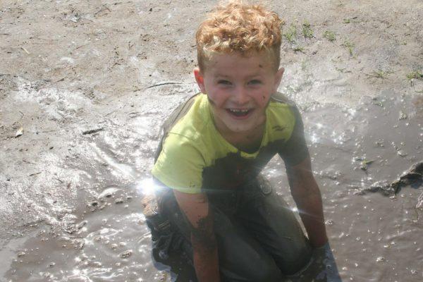 jongen in de modder bij kinderfeestje buiten in de natuur
