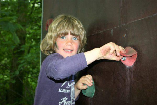 jongen op klimwand tijdens kinderfeestje