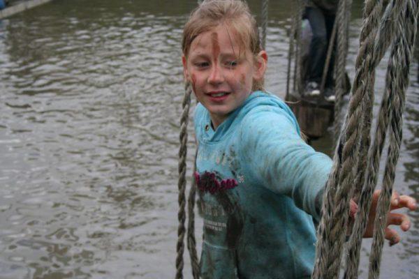 meisje op junglebrug boven water