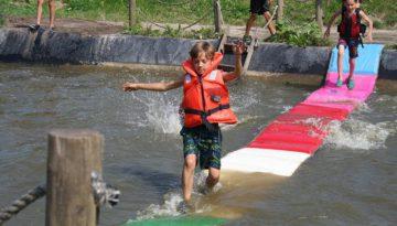 jongen met zwemvest loopt over watermat