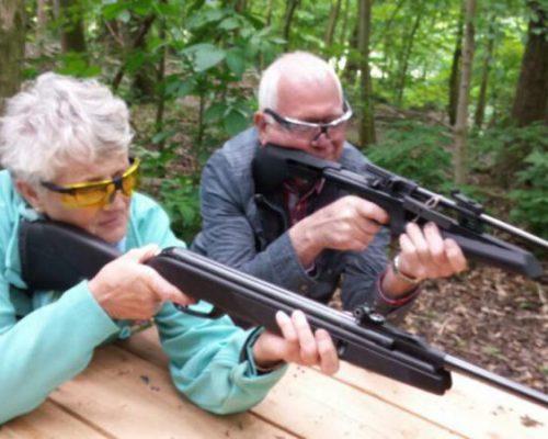 Man en vrouw met geweer tijdens schietworkshop op familiedag