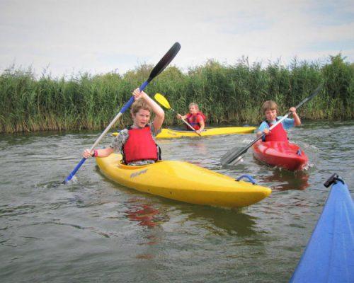 Kinderen in kayak tijdens watersport schoolreisje in Almere