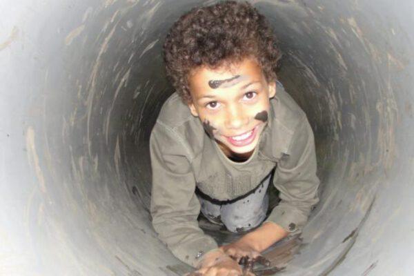 jongen kruipt door tunnel