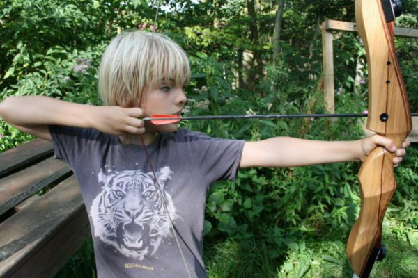 jongen richt met boogschieten