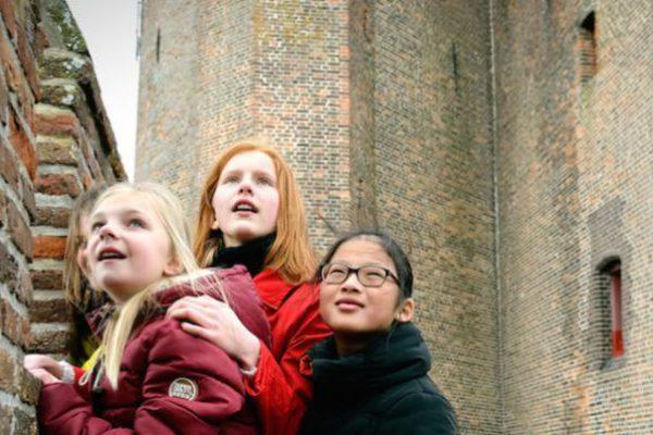 leerlingen voor de muur van kasteel Muiderslot
