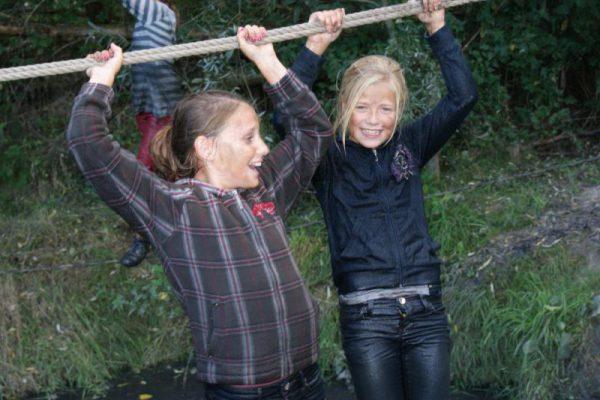 lachende meisjes op touwbrug bij outdoor feestje