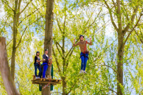 Jeugd klimt in klimpark in Almere tijdens schoolreisje