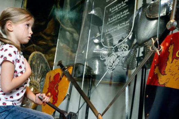 meisje bekijkt wapens in Muiderslot tijdens schoolreisje