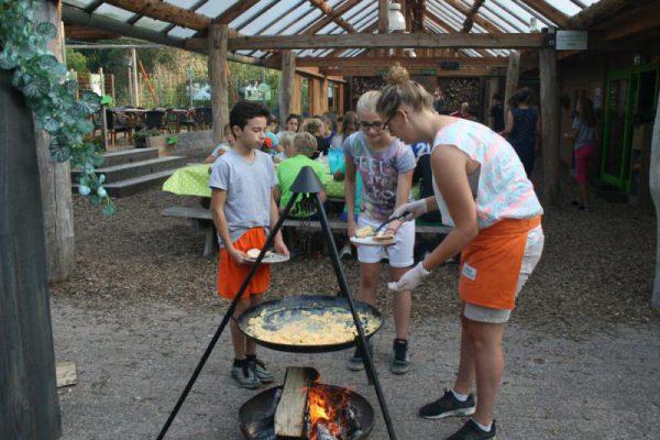 Kinderen halen eten bij kampvuur