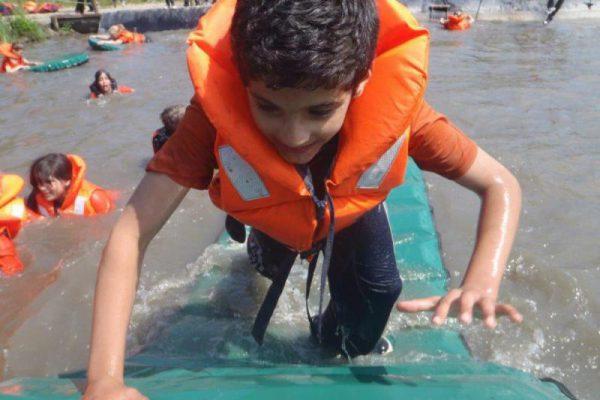 jongen met zwemvest in het water